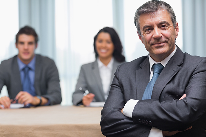 Businessman with arms crossed sitting with business panel in conference room