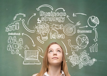 Blond girl near green chalkboard with business sketches