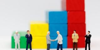 Miniature people handshake with step of Wood block stack.  agree